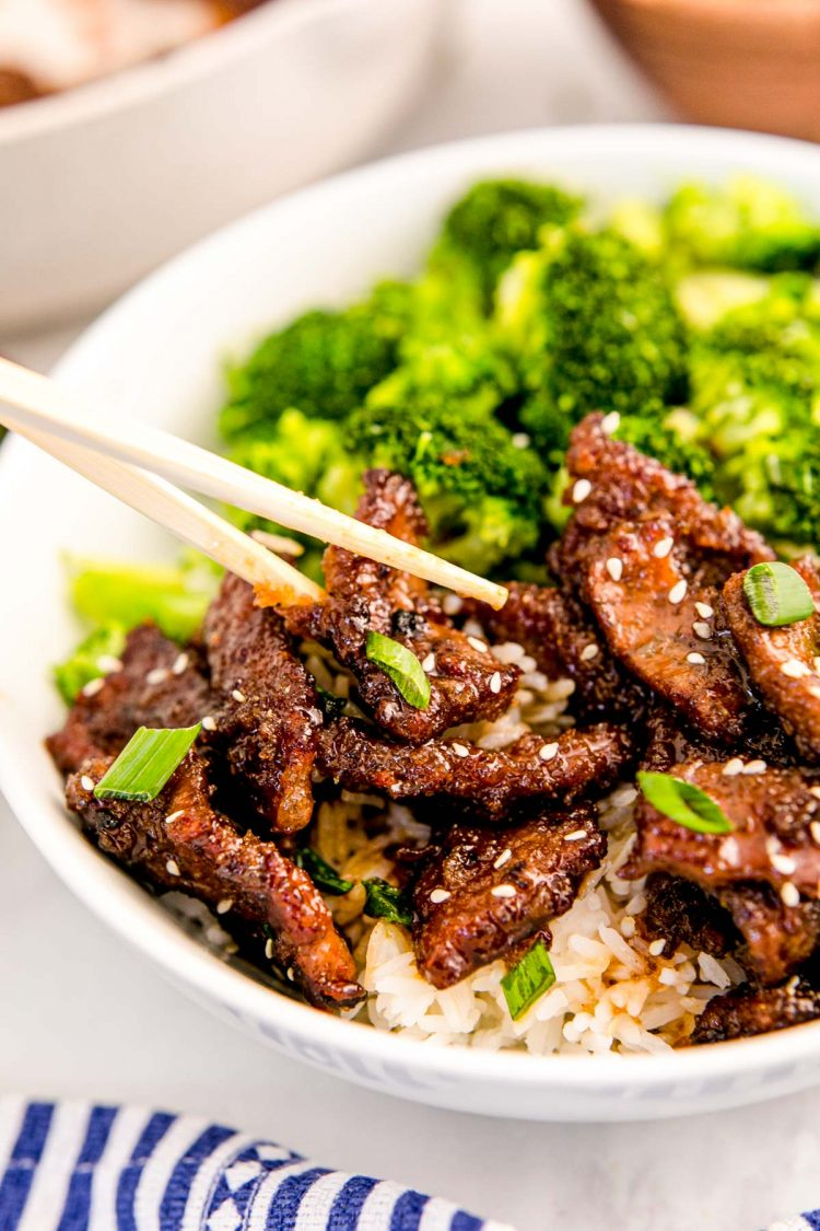 Chop sticks taking a piece of Mongolian beef out of a bowl.