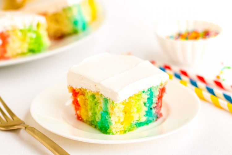 Close up photo of a slice of rainbow cake on a white plate.