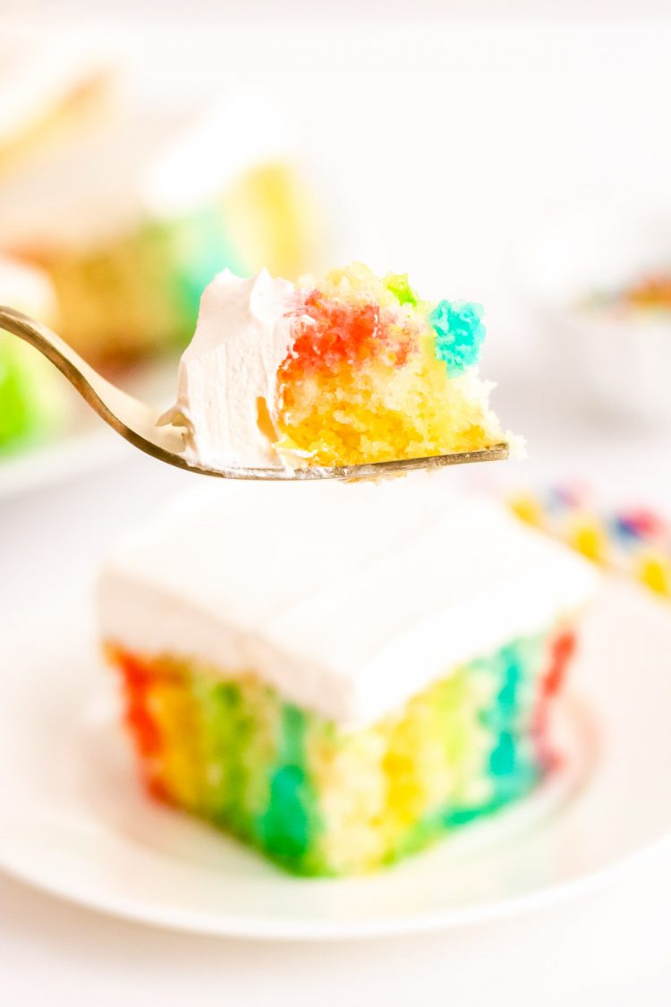 A bite of rainbow cake on a fork being held to the camera.