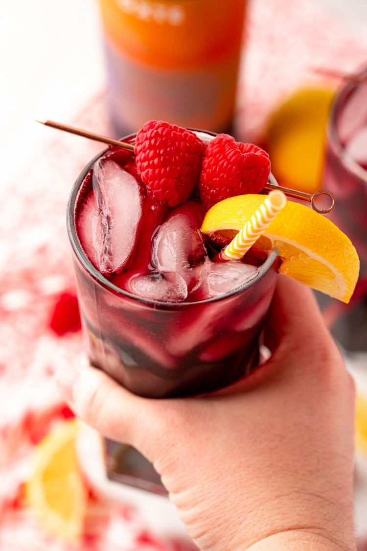 A woman's hand holding a red wine spritzer to the camera.