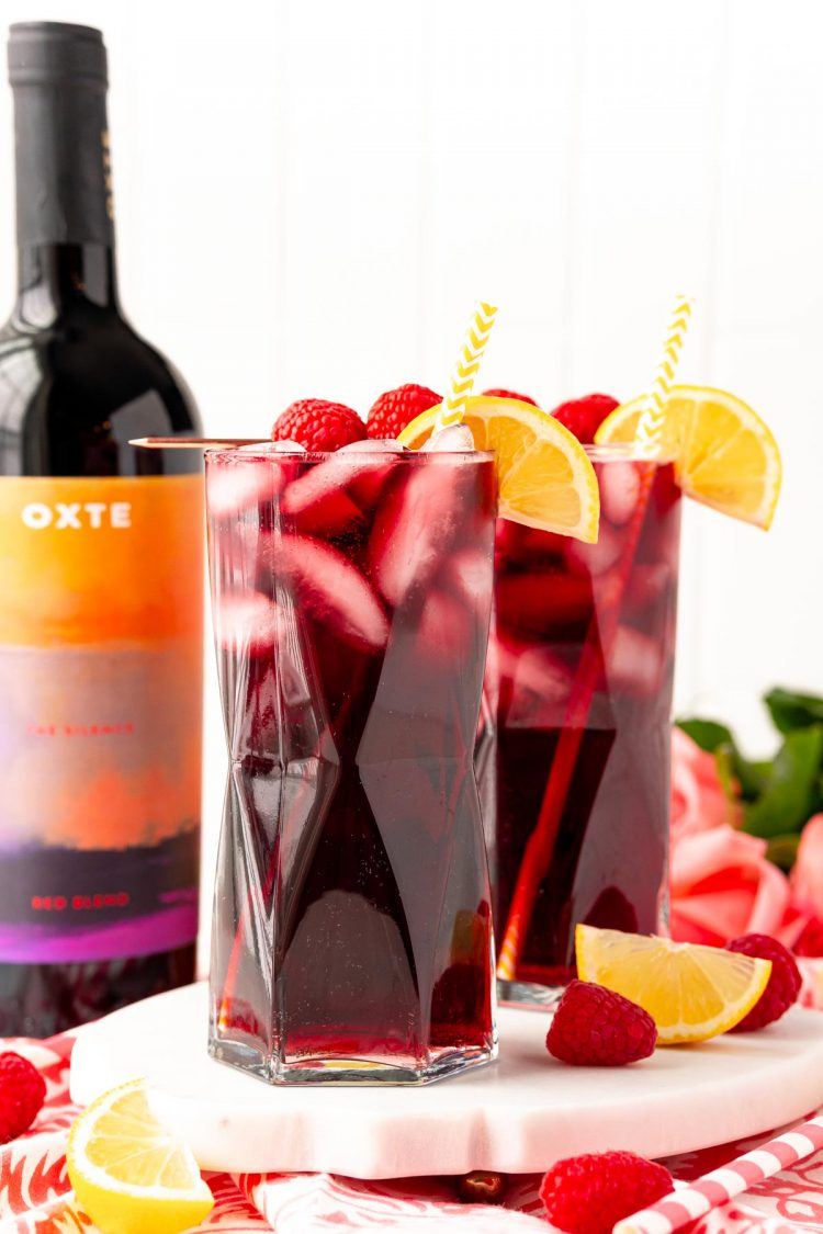 Straight on photo of two glasses filled with red wine spritzers on a marble tray with a bottle of red wine in the background.