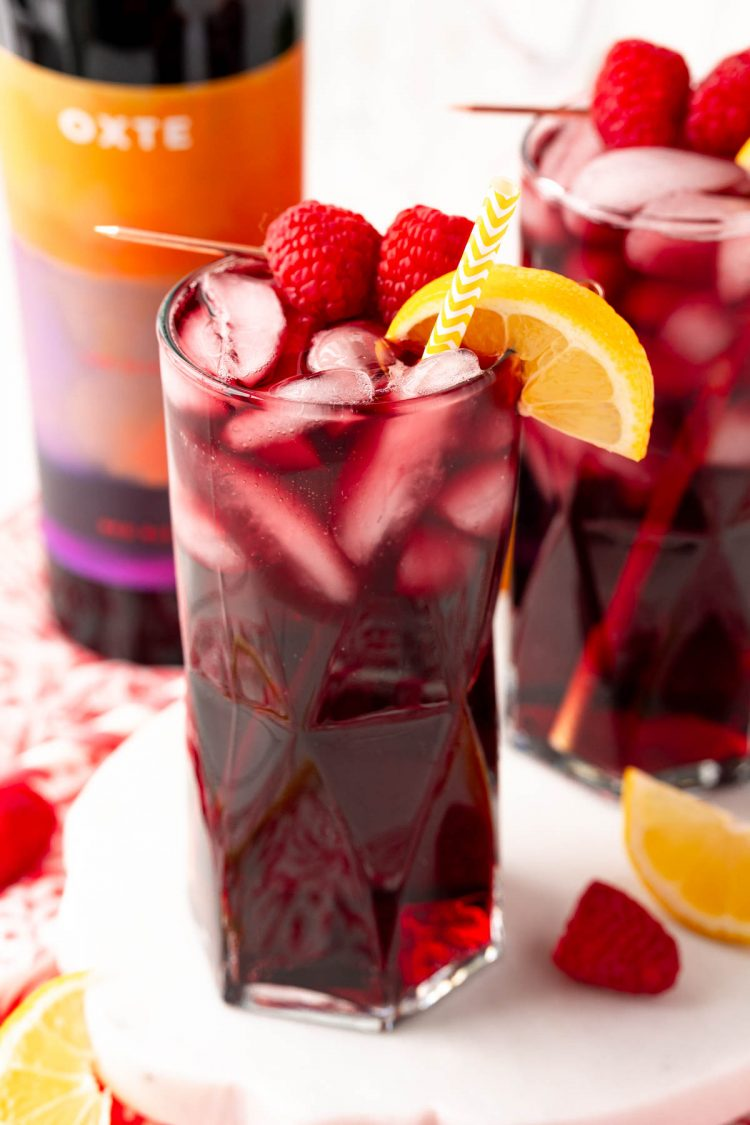 Close up photo of a red wine spritzer garnished with raspberries and lemon wedge.