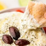 A piece of pita bread being dipped in a bowl of tzatziki sauce.