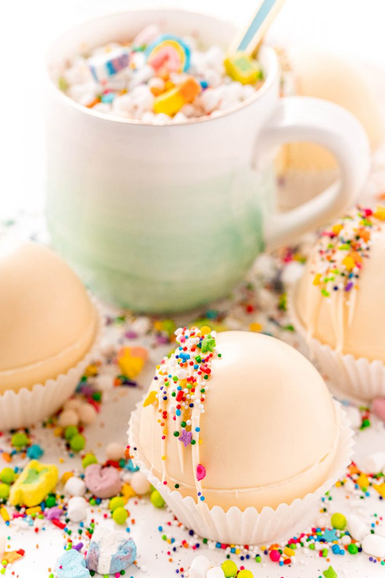 White hot cocoa bombs with a mug in the background surrounded by sprinkles and lucky charms marshmallows.