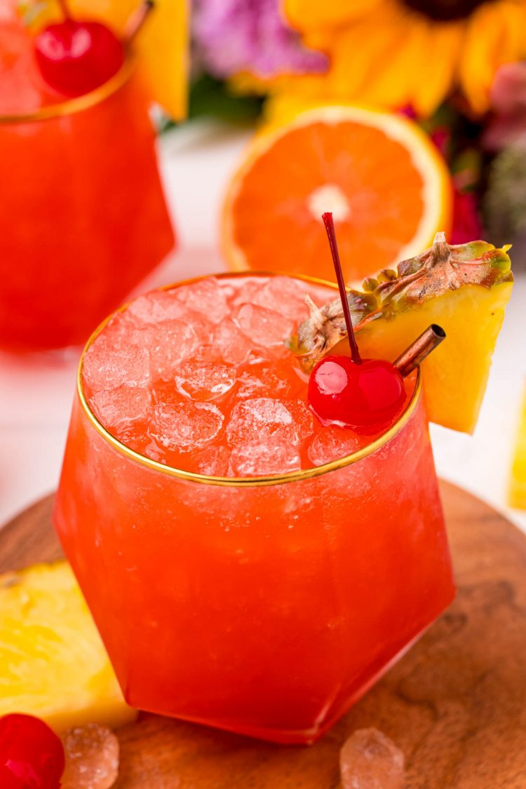 Close up photo of a gold rimmed glass with a bahama mama in it garnished with a maraschino cherry and a pineapple wedge.