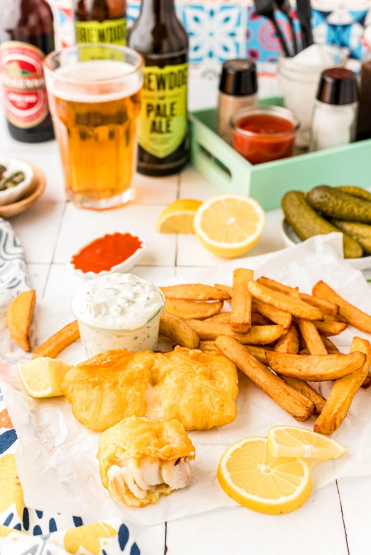 Fish and chips on a counter with beer and lemons and tartar sauce in the background.