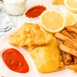 Pieces of fried fish on a white platter with fries and ketchup and lemon.
