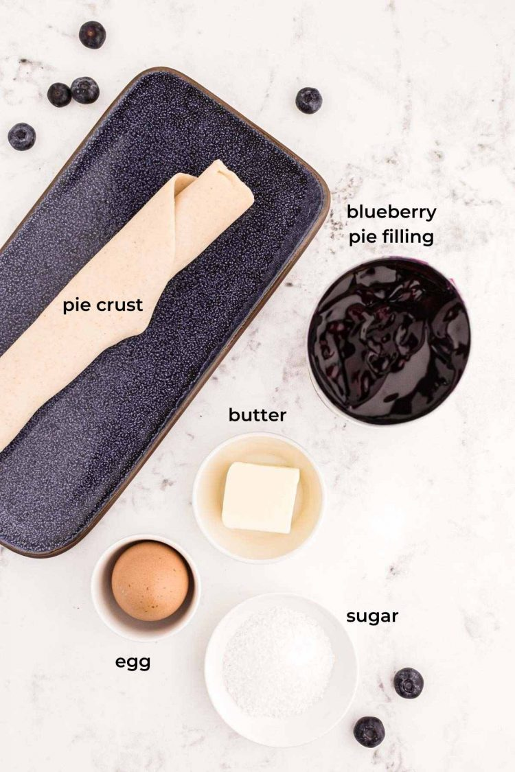 Ingredients to make blueberry hand pies on a marble counter.