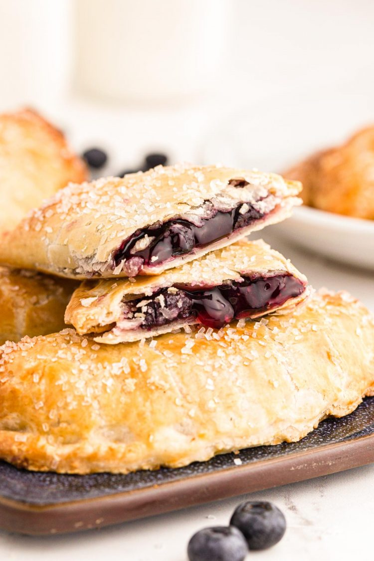 Photo of blueberry hand pies on a tray with a pie on top that's been split in half.