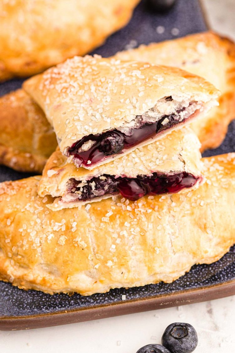 Close up photo of blueberry hand pies on a blue platter with one pie on top broken in half.