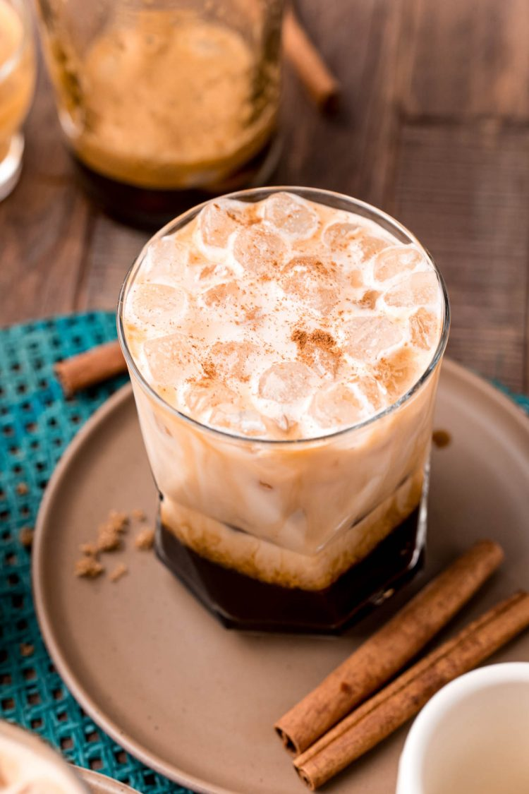 Close up photo of a brown sugar oatmilk shaken espresso on a brown plate with cinnamon sticks and brown sugar.