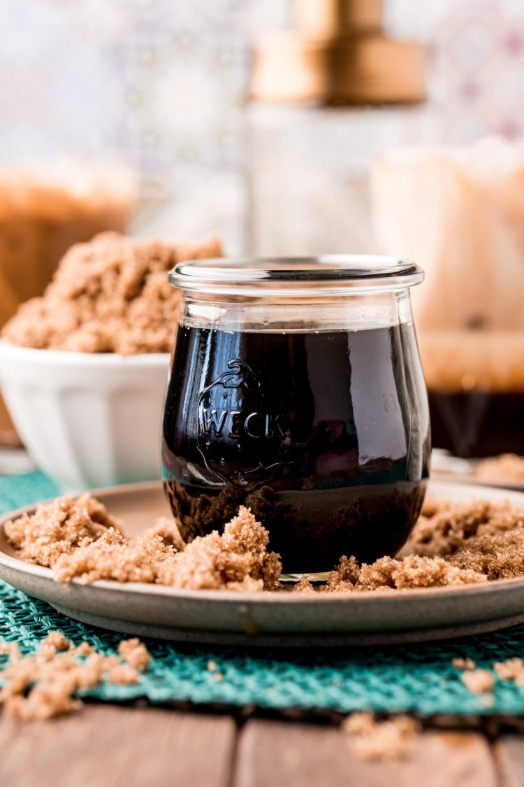 Close up photo of a jar of brown sugar simple syrup on a brown plate with brown sugar all around it.