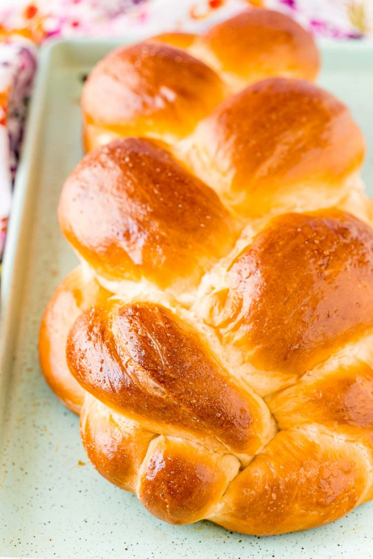 Close up photo of a loaf of Challah bread on a baking sheet.