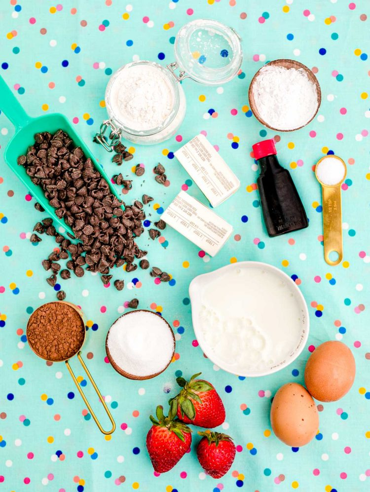Overhead photo of ingredients used to make chocolate waffles on a teal surface.