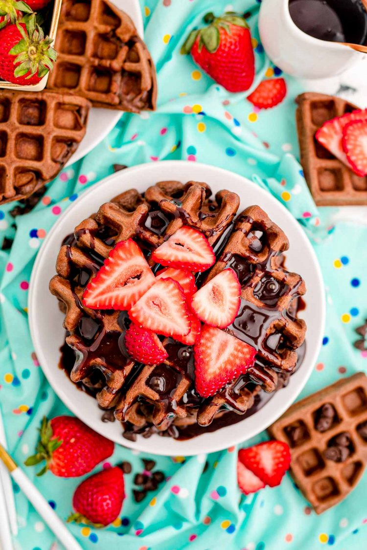 Overhead photo of a stack of chocolate waffles topped with chocolate syrup and strawberries.