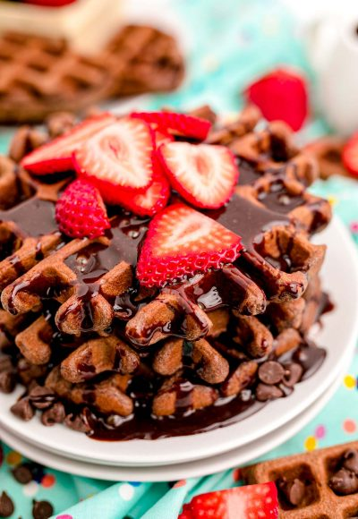 Close up photo of a stack of chocolate waffles with chocolate syrup and sliced strawberries on top.