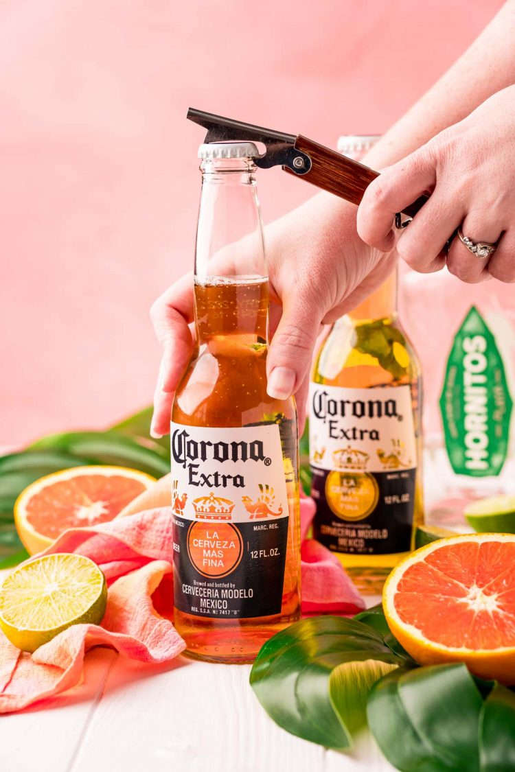 A woman popping the cap of a Corona off with a bottle opener.
