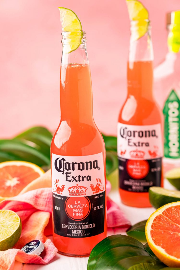 Close up photo of a Corona beer bottle with a Corona Sunrise in it and another one behind it.