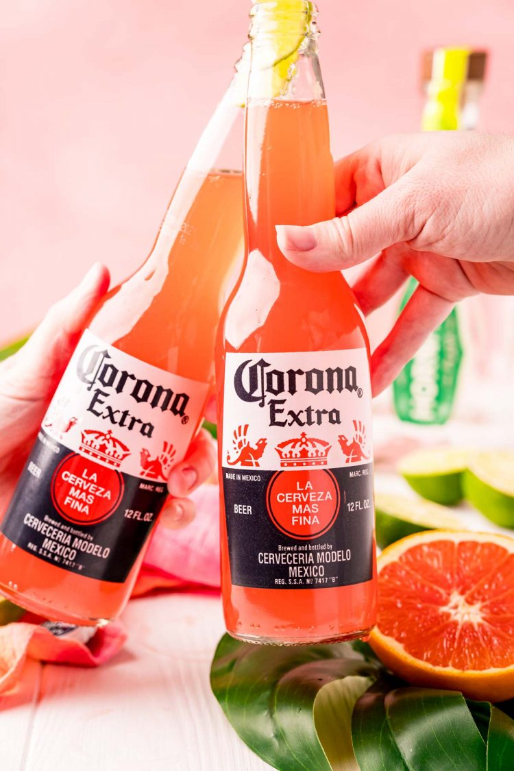 Two Corona bottles with Corona sunrises in them cheering.