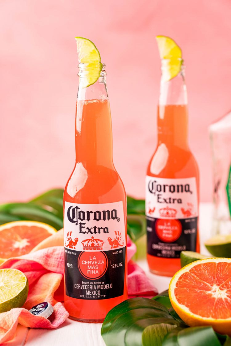 Close up photo of a Corona sunrise in a Corona bottle with citrus and palm leaves around it.