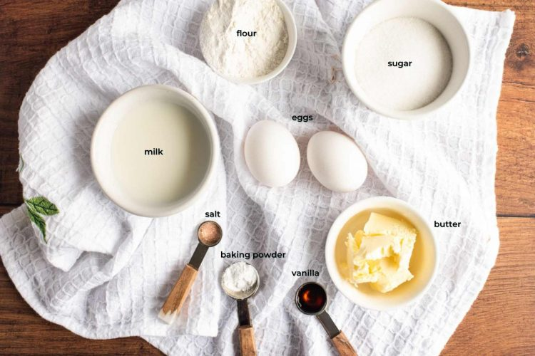 Ingredients used to make donut cookies arranged on a white kitchen towel on a wooden table.