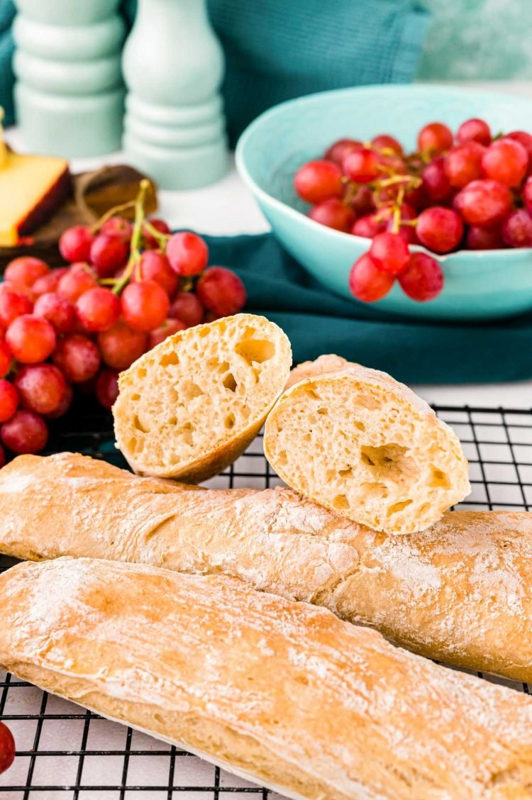 Three French baguettes on a black wire rack, one has been cut in half and you can see the inside. Grapes in the background.