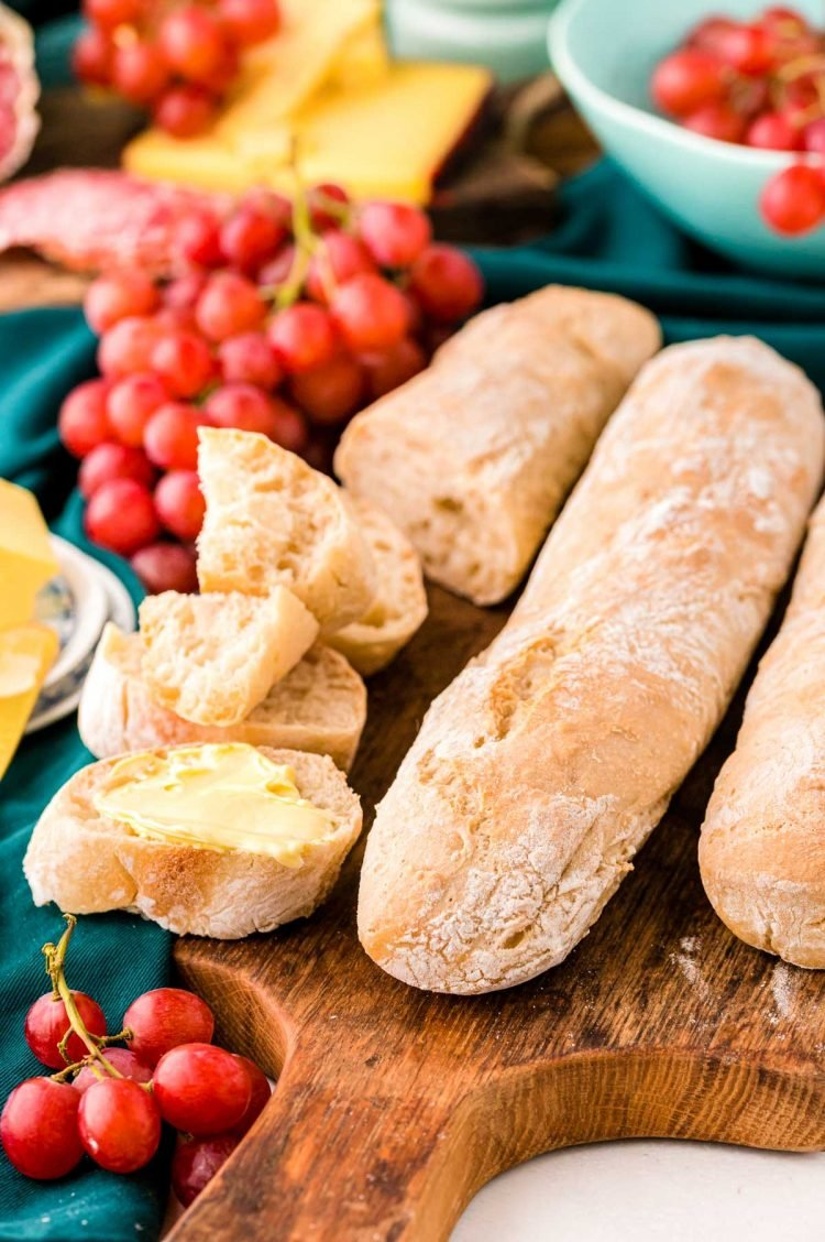 French Baguettes on a wooden cutting board, one has been sliced up and has butter on it.