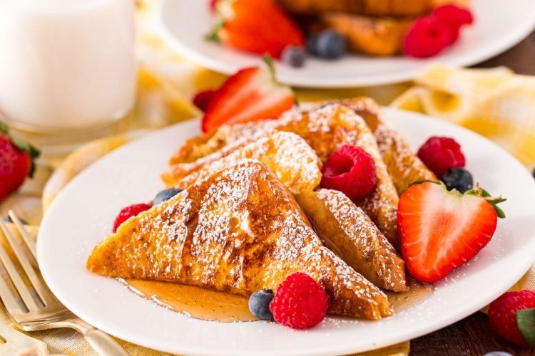 Close up photo of French toast on a white plate with berries.