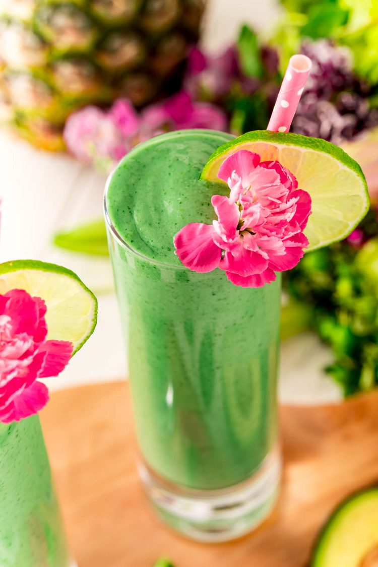 Close up photo of green smoothie with a pink carnation, lime slice, and pink straw.