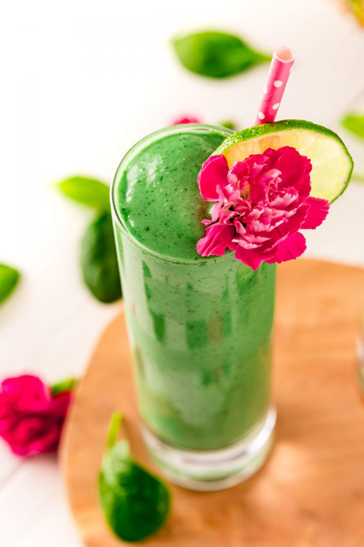 Close up photo of a green smoothie in a tall glass garnished with a pink carnation and lime slice.