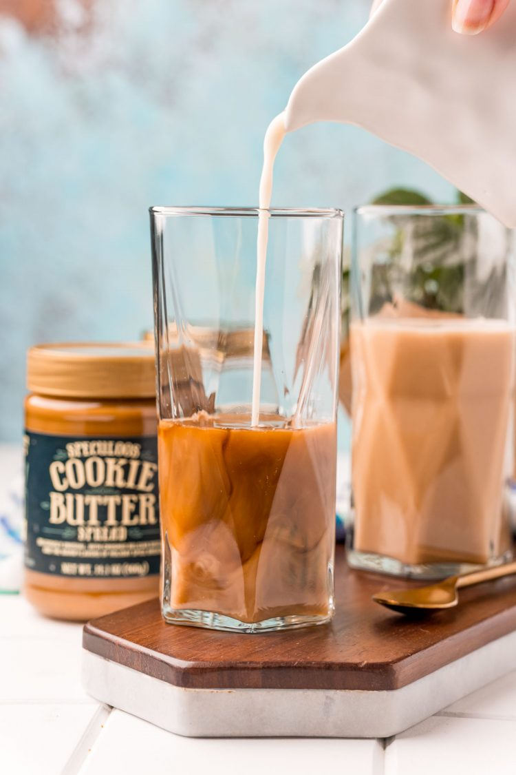 Oat milk being poured into a tall glass to make a cookie butter latte.