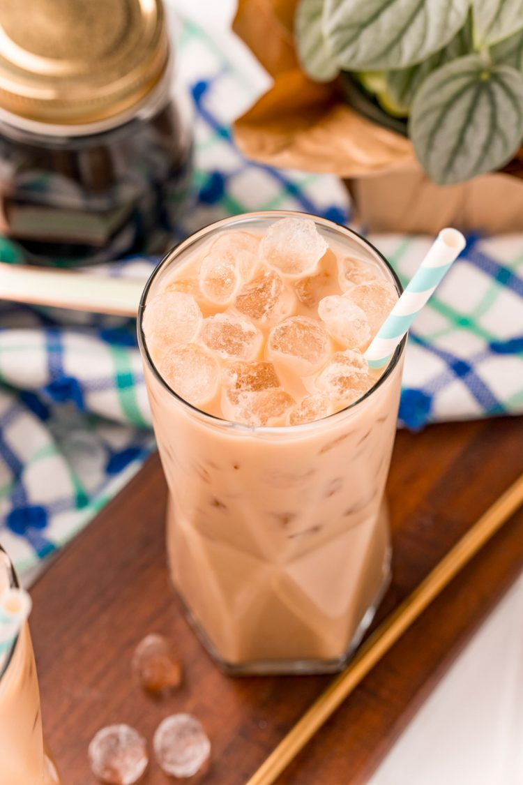Close up photo of a cookie butter latte in a glass with a blue and white napkin in the background.