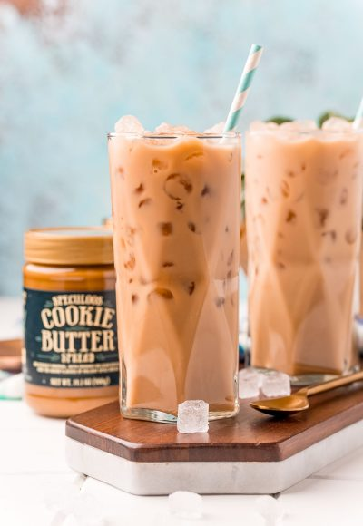 Straight on photo of two glasses filled with iced cookie butter lattes and a jar of cookie butter next to it.