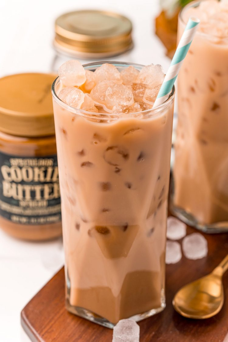 Close up photo of an iced cookie butter latte with a blue and white paper straw.