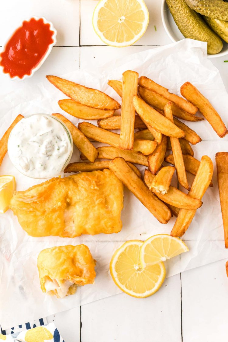 Overhead photo of fish and chips on a white table.