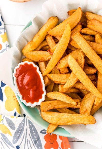 Close up overhead photo of french fries in a bowl with a mini bowl of ketchup.