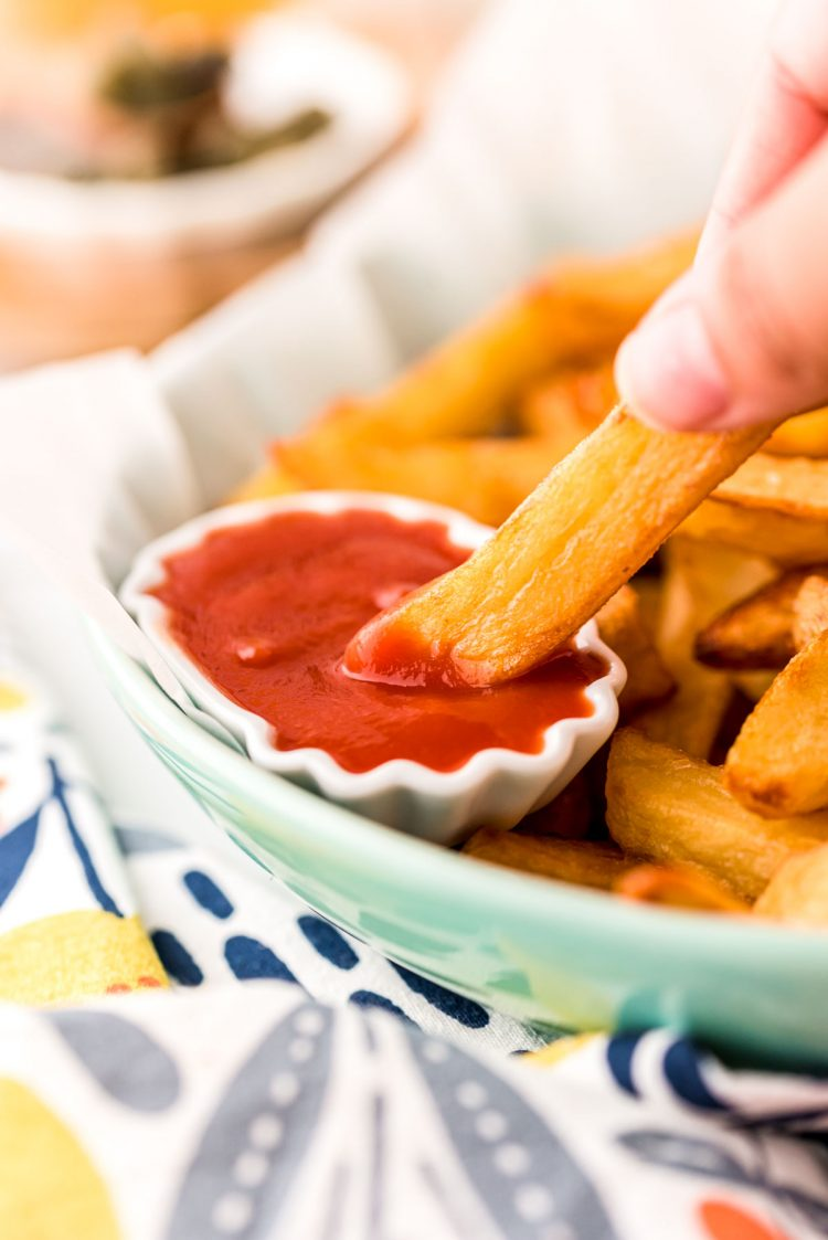 Close up photo of a hand dipping a French fry in ketchup.
