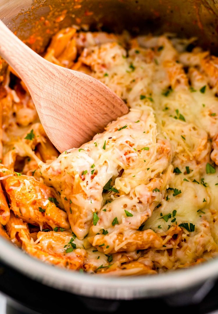 Close up photo of a wooden spoon scooping into an instant pot with chicken parmesan pasta in it.