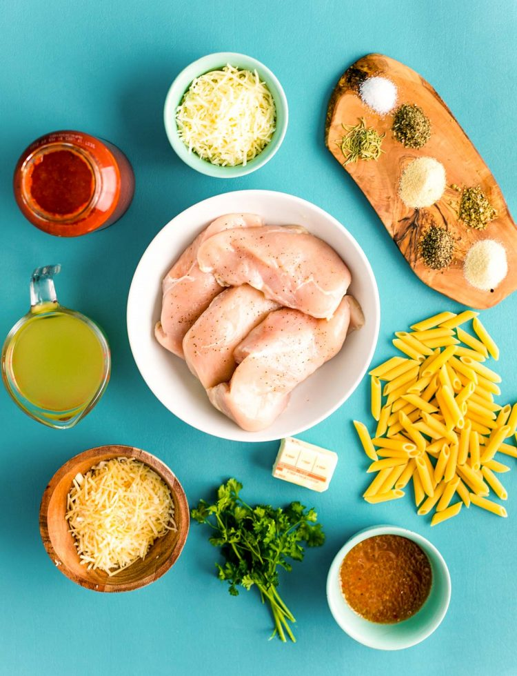 Overhead photo of ingredients prepped to make chicken parmesan pasta in an instant pot on a teal background.