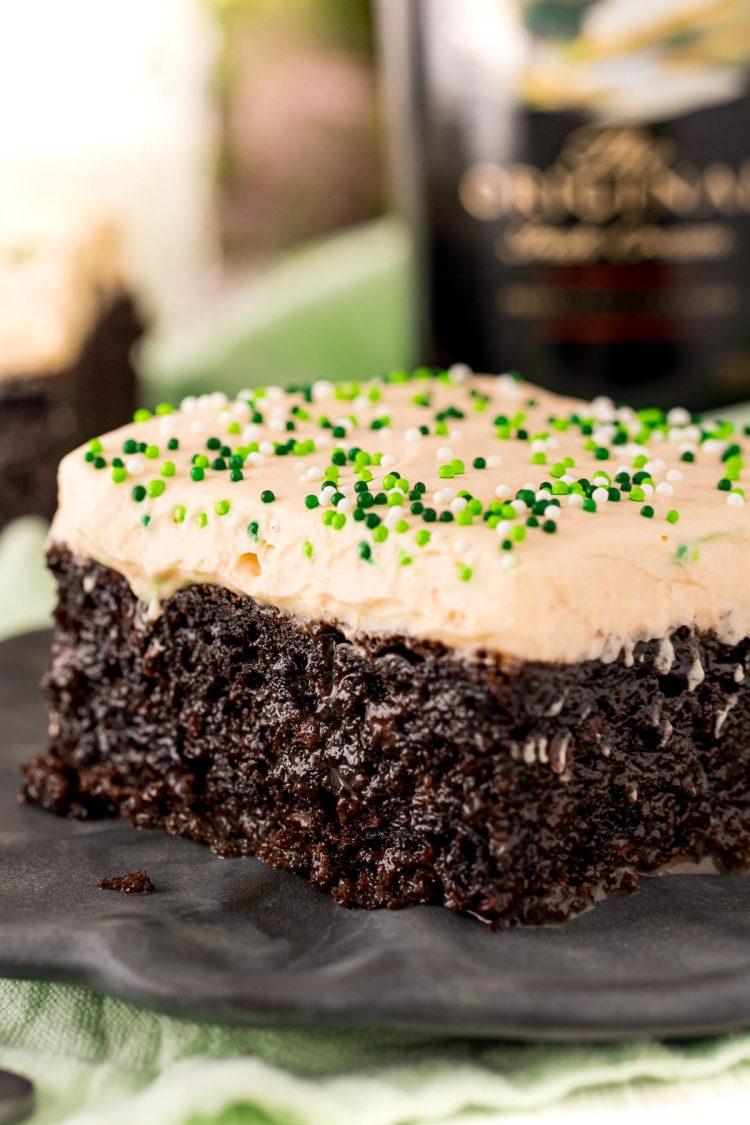 Close up photo of a slice of chocolate cake with irish cream frosting.