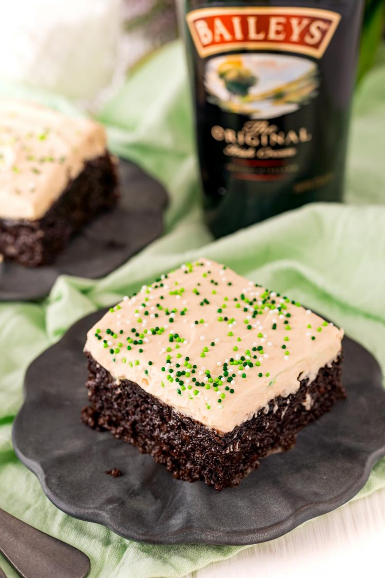 Irish cream cake slice on a black plate with a bottle of Bailey's in the background.