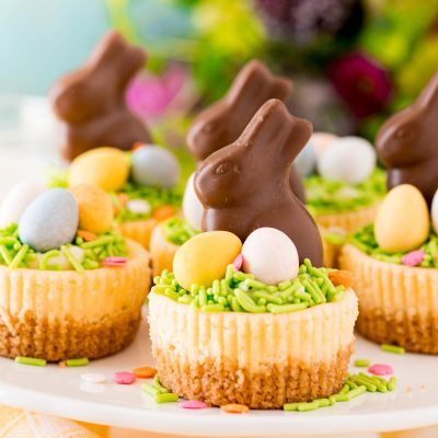 Easter cheesecakes topped with cadbury eggs and chocolate bunnies on a white cake stand.