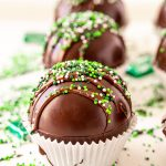 Close up photo of mint hot chocolate bombs on a white surface with green sprinkles and chocolate mints scattered around.