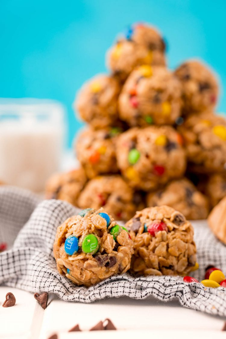 Close up photo of monster cookie energy balls on a table with a plate of them in the background with a glass of milk.