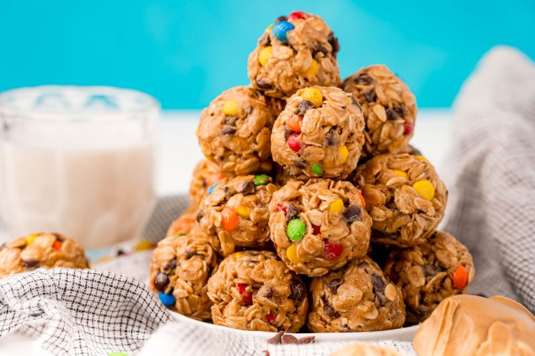 Monster cookie energy balls on a white plate on a gray napkin.