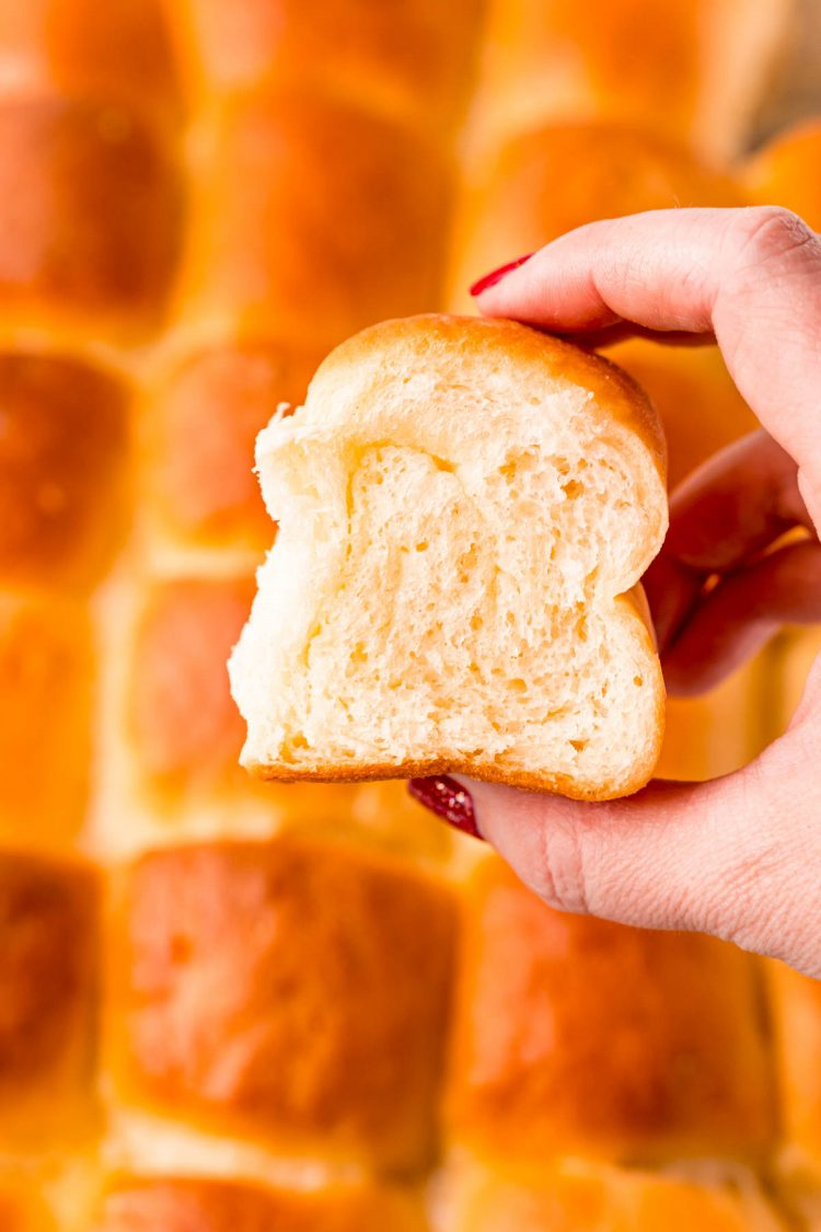 A woman's hand holding up a dinner roll to the camera with more rolls in the background.