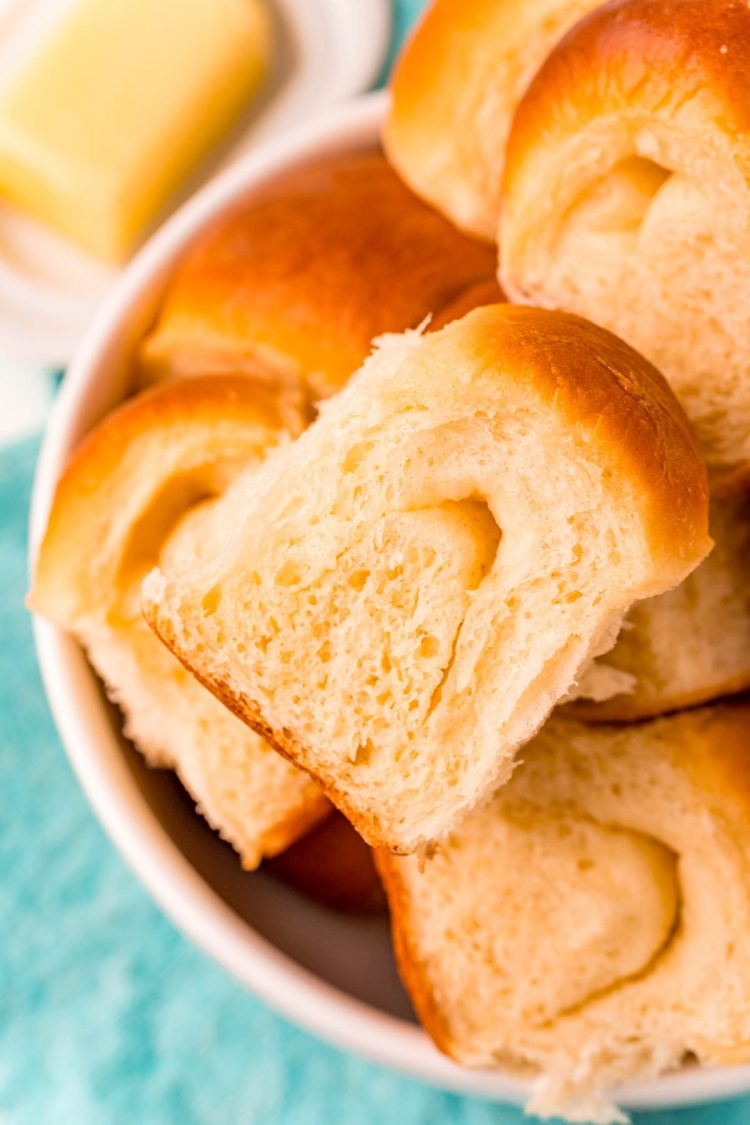 Close up photo of parker house rolls piled in a white bowl on a teal napkin.