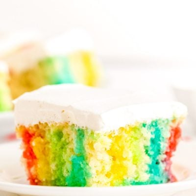 This Rainbow Jello Poke Cake is easily made using a boxed white cake mix and jello to create a fun, light dessert filled with vibrant colors!