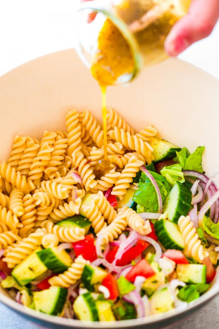 A woman's hand pour dressing into a bowl with ingredients for pasta salad.