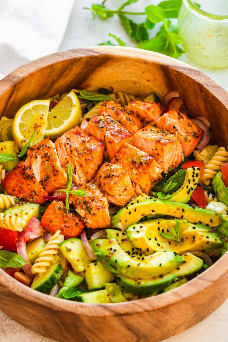 Salmon pasta salad in a wooden serving bowl.